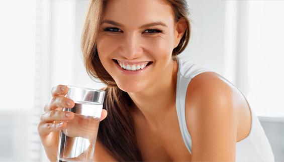 Frau trinkt Wasser bei Verstopfung